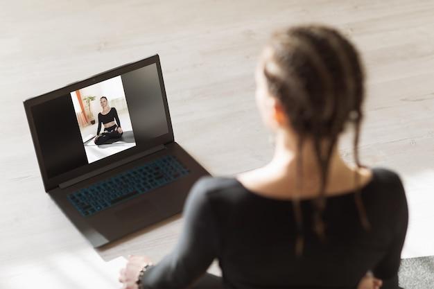 Uma mulher está fazendo ioga online em casa com um instrutor sobre o tema de treinamento remoto
