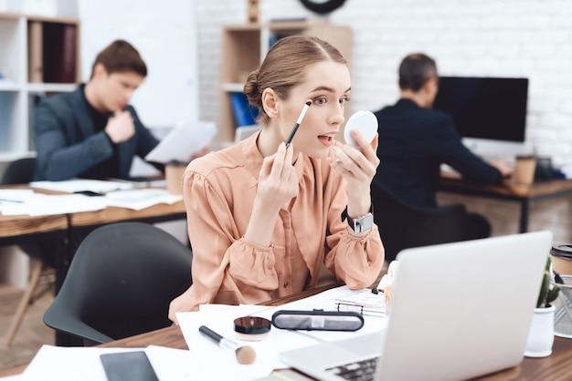 Uma mulher está fazendo maquiagem no seu local de trabalho.
