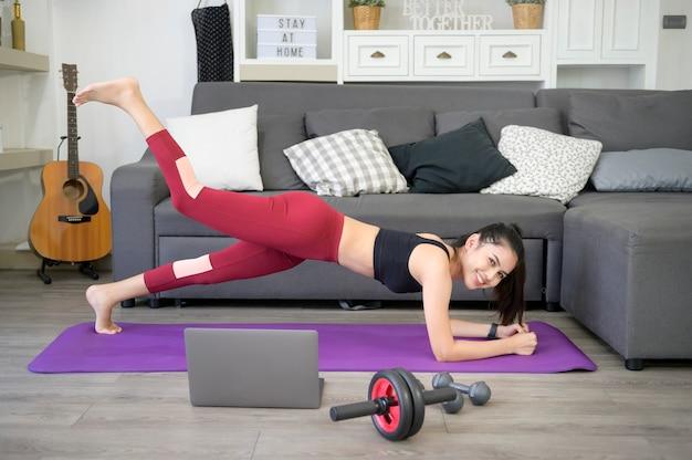 Uma mulher está fazendo prancha de ioga e assistindo a tutoriais de treinamento on-line em seu laptop na sala de estar, exercícios de fitness em casa, conceito de tecnologia de cuidados de saúde.