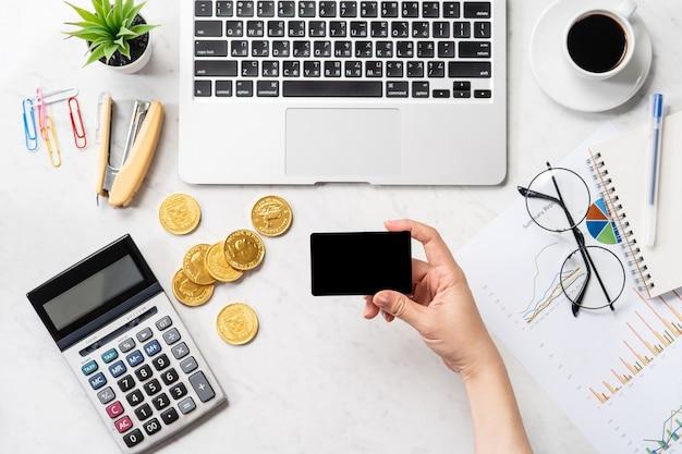 Uma mulher está fazendo um pagamento online com cartão e smartphone isolados em uma mesa de escritório de mármore moderna