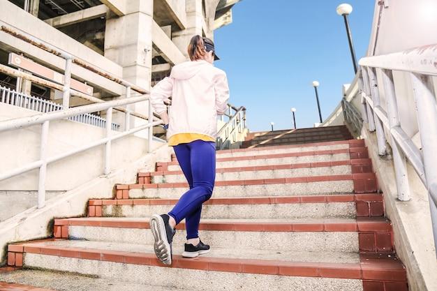 Uma mulher está intensificando de escadas perto de um grande estádio como pano de fundo