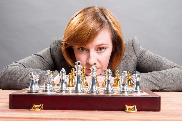 Uma mulher está jogando xadrez. empresário joga xadrez