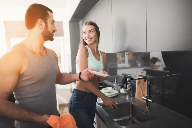 Uma mulher está lavando pratos, um homem está limpando.