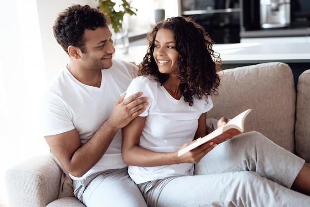 Uma mulher está lendo um livro, um homem está sentado e abraçando-a.