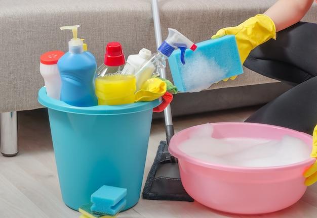 Uma mulher está limpando a casa, no apartamento, segurando uma esponja sobre uma bacia com detergente diluído