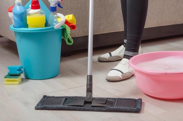 Uma mulher está limpando a casa, o apartamento, lava o piso de parquete com esfregão e detergente.