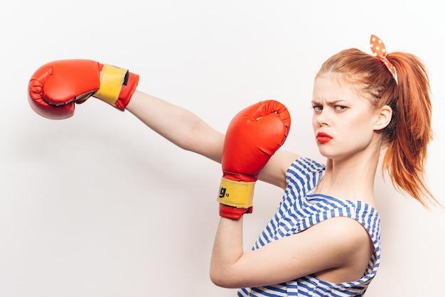 Uma mulher está lutando boxe em um fundo claro maquiagem brilhante penteado camiseta listrada