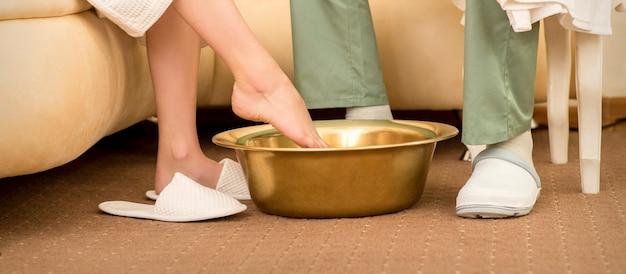 Uma mulher está mergulhando os pés em uma tigela antes de lavar a terapia dos pés