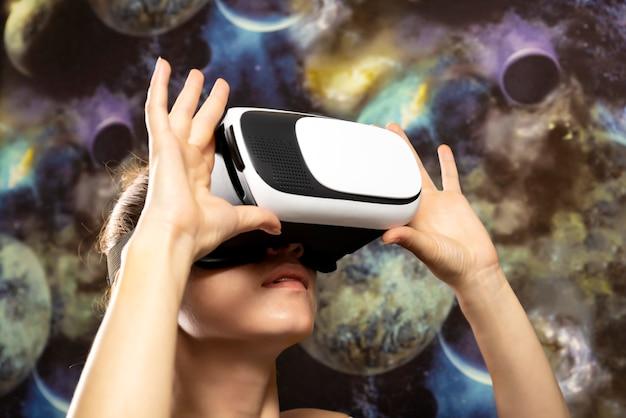 Uma mulher está olhando através da realidade virtual no espaço. fundo do espaço