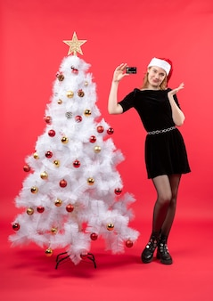 Uma mulher está parada ao lado da árvore de natal