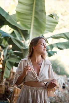 Uma mulher está perto de folhas verdes de bananeira na ilha. árvores tropicais
