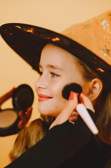 Uma mulher está pintando no rosto da menina a maquiagem de um gatinho para uma festa no haloween