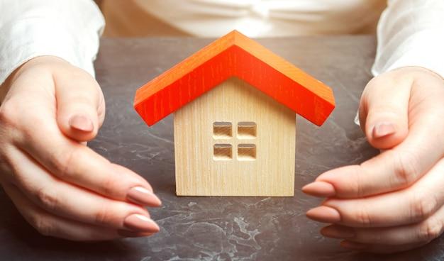 Uma mulher está protegendo uma casa de madeira em miniatura.