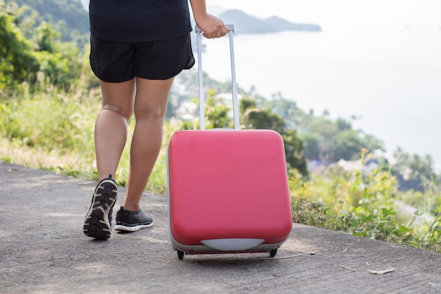 Uma mulher está puxando uma mala com vista para o mar.