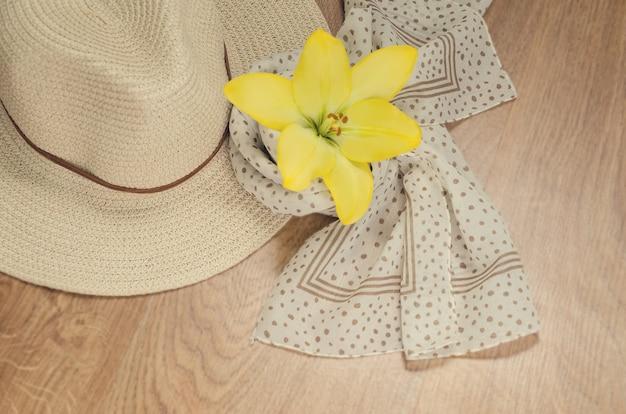 Uma mulher está saindo de férias ou em viagem - um chapéu e um lenço leve com bolinhas. humor romântico. tons quentes. camada plana. vista de cima