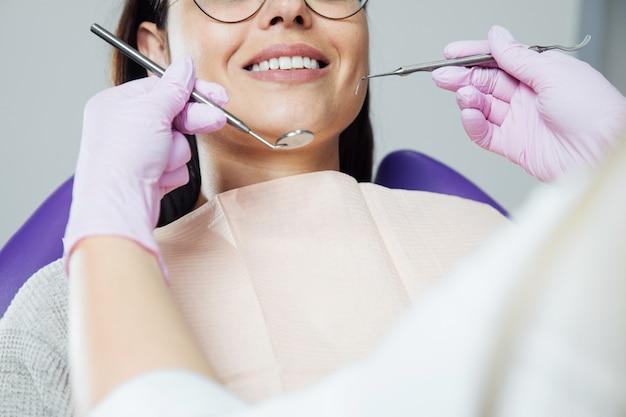 Uma mulher está se preparando para um exame dentário. mulher que tem os dentes examinados em dentistas.