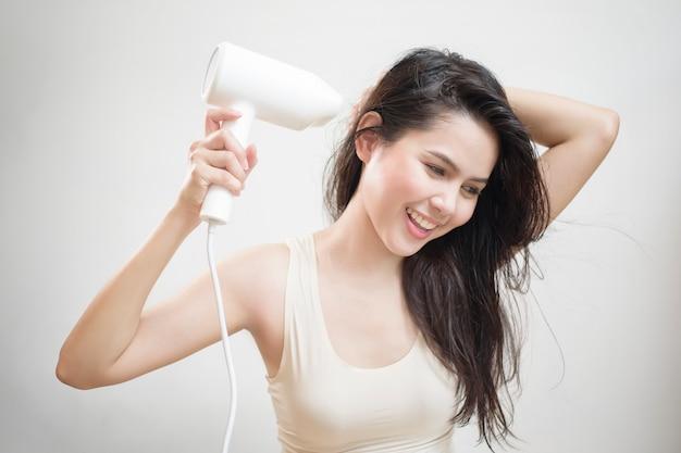Uma mulher está secando o cabelo depois do banho