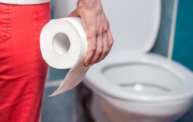 Uma mulher está segurando papel higiênico. o conceito de diarréia. prisão de ventre.