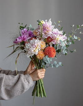 Uma mulher está segurando um buquê festivo com flores de crisátamo nas mãos