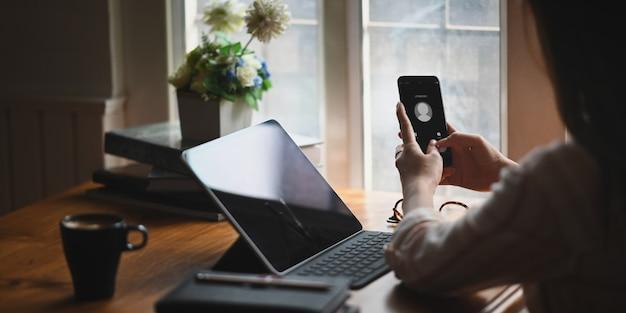 Uma mulher está segurando um telefone celular com uma chamada de um chamador desconhecido.