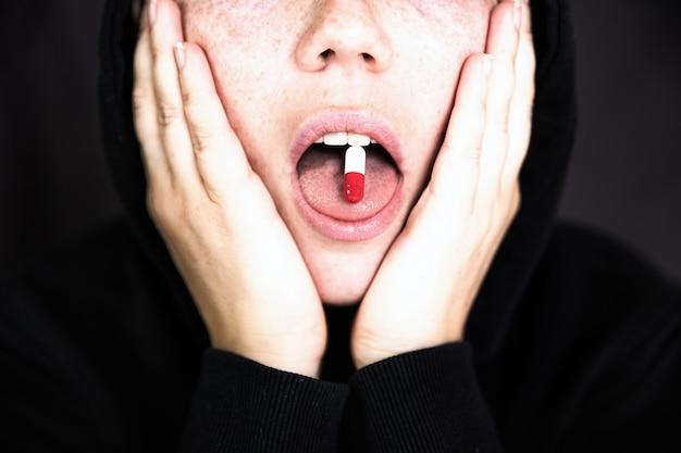 Uma mulher está segurando uma cápsula de comprimido com um medicamento em sua língua adolescente tomando xtccocaína outros medicamentos