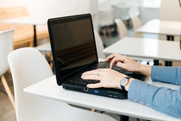 Uma mulher está sentada à mesa e algo está digitando em um laptop