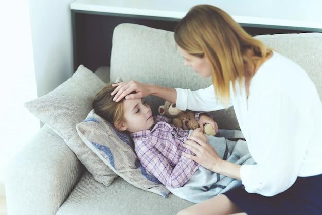 Uma mulher está sentada ao lado de uma menina que está doente.