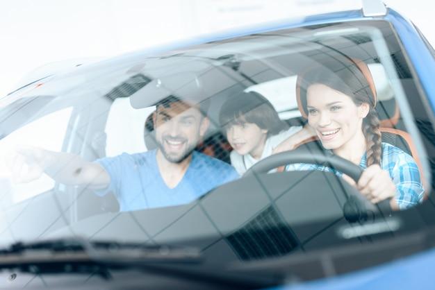 Uma mulher está sentada ao volante de um carro novo.