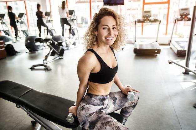 Uma mulher está sentada em um aparelho de treinamento