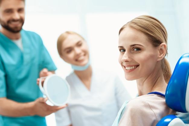 Uma mulher está sentada em um consultório odontológico em uma cadeira odontológica.