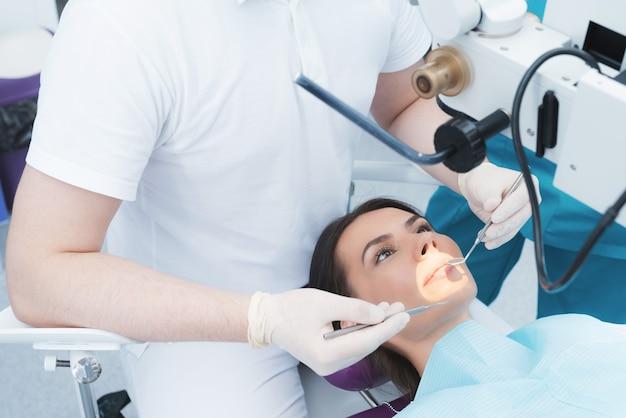 Uma mulher está sentada em uma cadeira odontológica na recepção de um dentista.