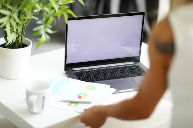 Uma mulher está sentada em uma mesa branca em frente a um laptop em funcionamento e documentos com um diagrama estão no
