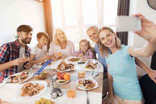 Uma mulher está sentada em uma mesa festiva e fazendo um selfie