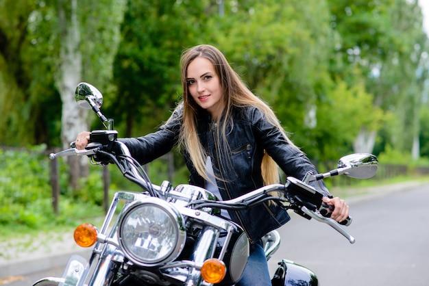Uma mulher está sentada em uma motocicleta e sorrindo.
