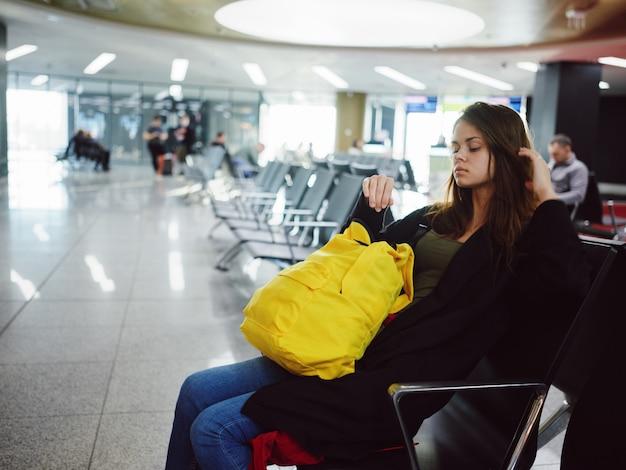 Uma mulher está sentada no aeroporto com uma mochila amarela à espera de um voo