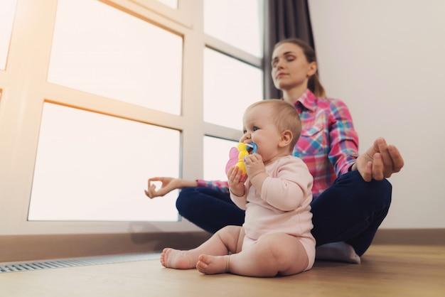 Uma mulher está sentada no chão com o bebê e meditando.