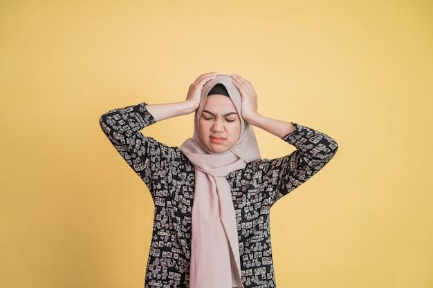 Uma mulher estressada usando hijab com as duas mãos segurando a cabeça enquanto está de pé