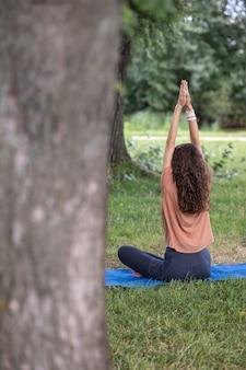 Uma mulher européia esportiva pratica ioga e meditação em um parque ou lugar público; uma mulher pratica esportes