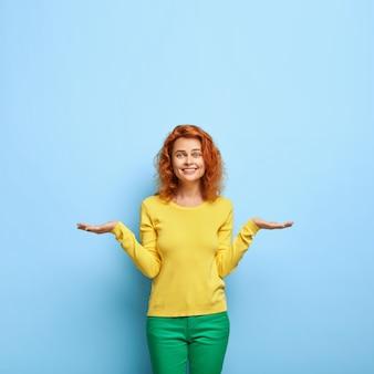 Uma mulher europeia positiva e satisfeita com um penteado ruivo levanta duas palmas como se segurasse algo e escolhesse entre dois objetos invisíveis vestidos com um moletom amarelo sobre o espaço em branco da parede azul