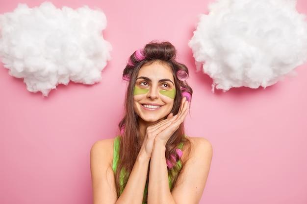 Uma mulher europeia satisfeita mantém as mãos perto do rosto, tem uma expressão facial suave, aplica adesivos de colágeno para reduzir o inchaço, tem uma expressão sonhadora isolada sobre a parede rosa