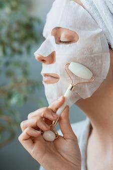 Uma mulher europeia se senta em frente a um espelho e massageia o rosto com um massageador de mão de cerâmica.