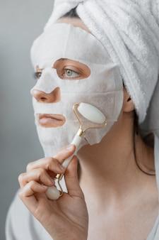Uma mulher europeia se senta em frente a um espelho e massageia o rosto com uma mão de cerâmica