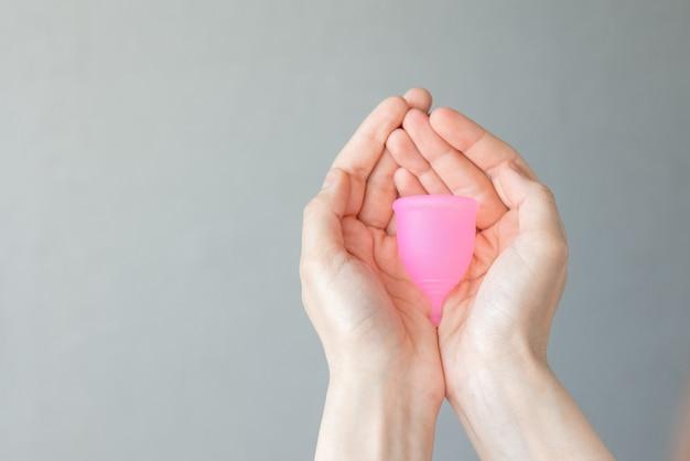 Uma mulher europeia segura nas mãos um copo menstrual rosa feito de silicone para higiene e cuidados femininos