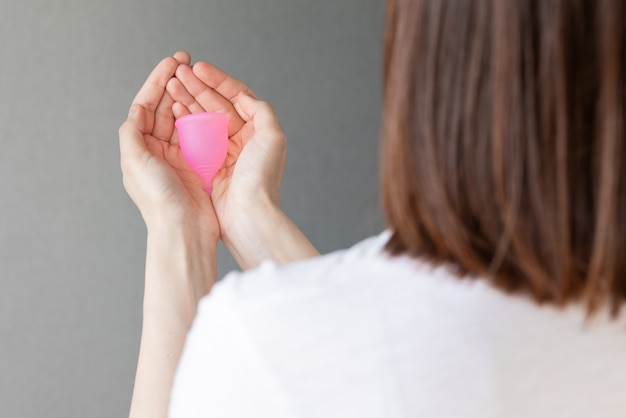 Uma mulher europeia segura nas mãos um copo menstrual rosa feito de silicone