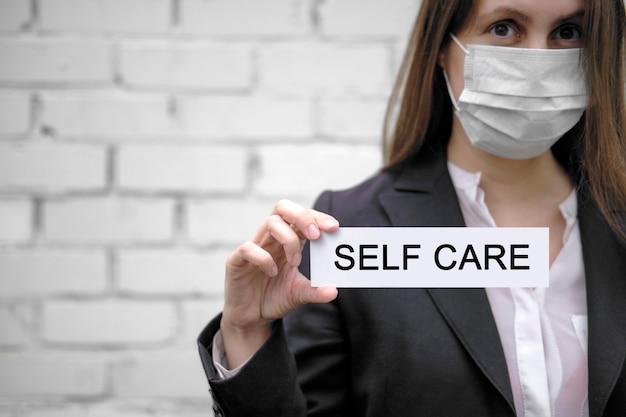 Uma mulher europeia usando uma máscara médica segura uma placa com a inscrição auto-cuidado