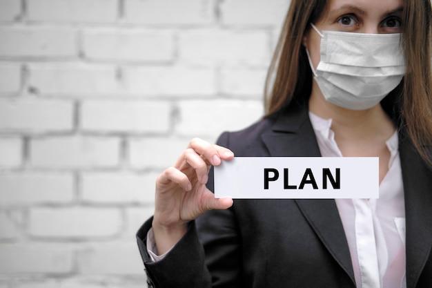 Uma mulher europeia usando uma máscara médica segura uma placa com a inscrição plano