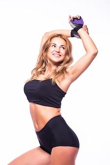 Uma mulher exercitando zumba fitness dançando em silhueta na parede branca