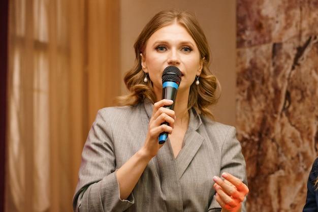 Uma mulher fala ao microfone, dá uma palestra sobre negócios. conferência treinamento seminário negócios apresentação apresentação audiência.