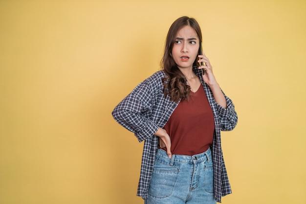 Uma mulher falando em uma chamada usando um telefone celular com uma expressão de raiva