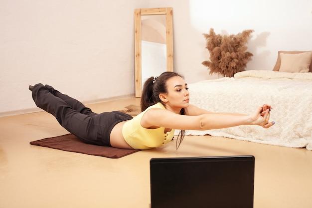 Uma mulher faz exercícios para perder peso. cursos de fitness online. olha para o laptop